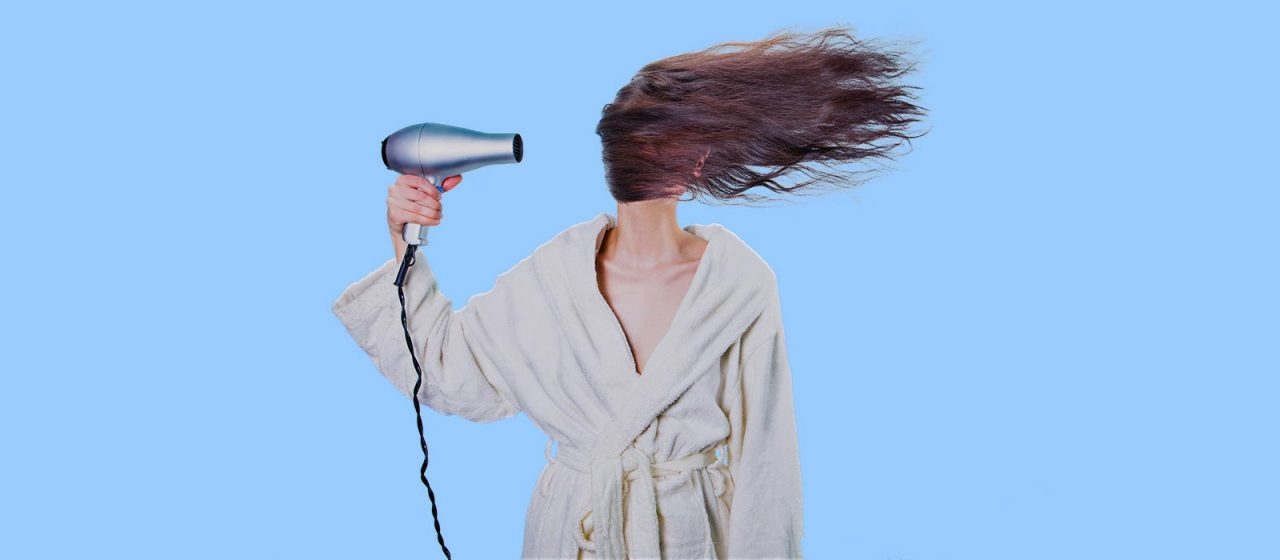 Woman blow drying her damaged hair