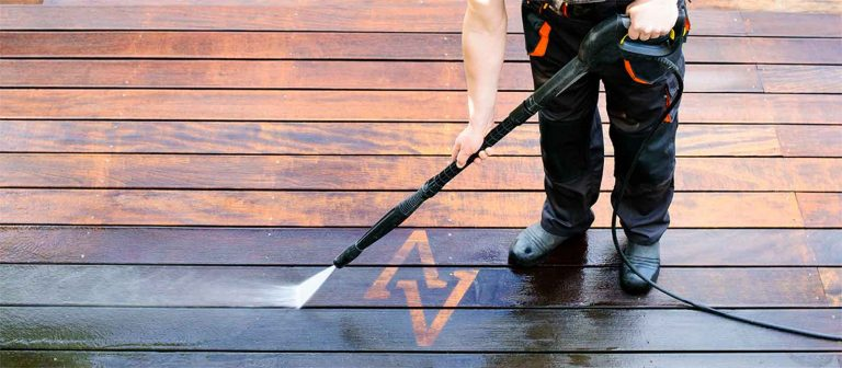 man using best pressure washer to clean patio decking showing before and after