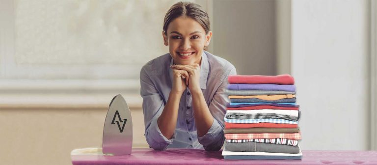 Woman with steam generator iron and neat pile of clothes looking happy