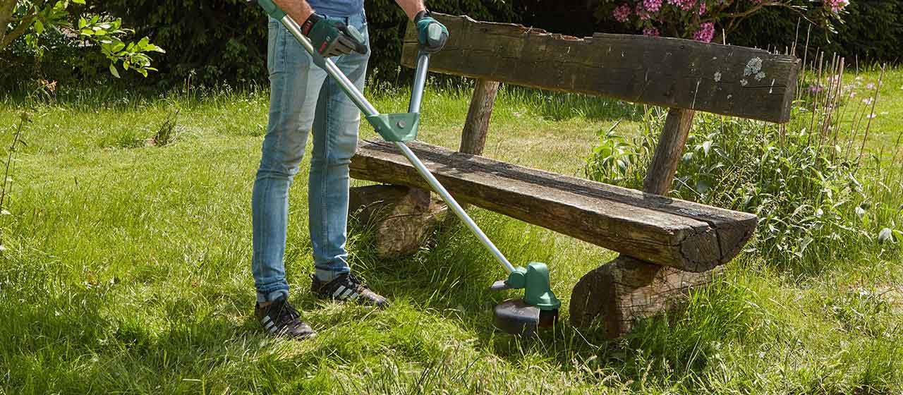 man in uk garden using grass trimmer to cut grass around and under bench. image credit: Bosch