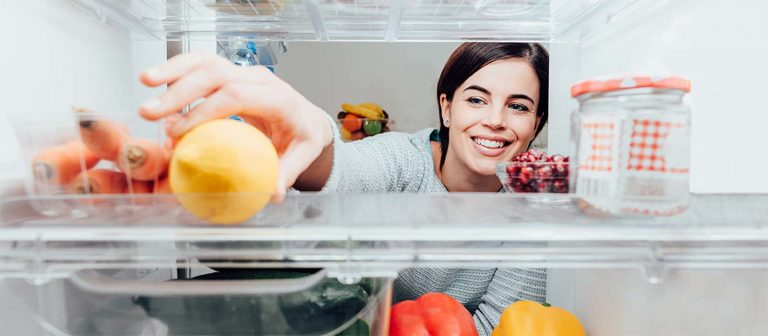 best under counter fridge recommended to fit beneath your worktop with happy person taking fruit from inside new refrigerator uk